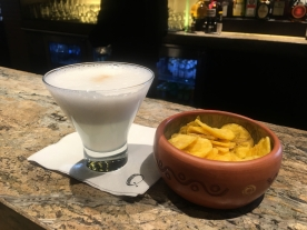 pisco sour and plantain chips at the bar